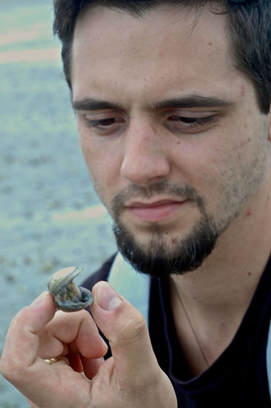 Unitec student Dyllan Cochrane examines a gaping dead cockle. Dyllan is likely to study this cockle die-off event as part of his undergraduate research.